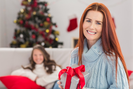 Festive mother holding a gift at home in the living room photo