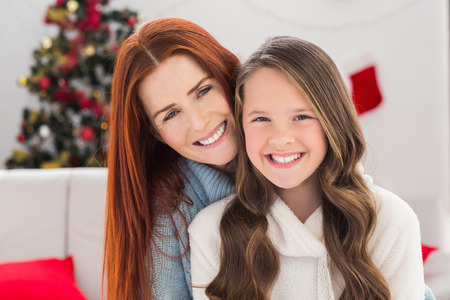 Festive mother and daughter on the couch at home in the living room photo