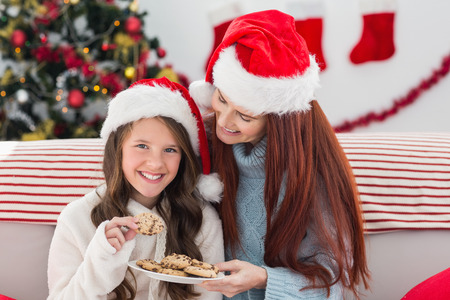 Festive mother and daughter on the couch with cookies at home in the living room photo