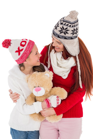 Mother and daughter holding teddy bear on white background photo