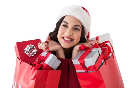 Excited brunette holding shopping bags full of gifts on white background photo