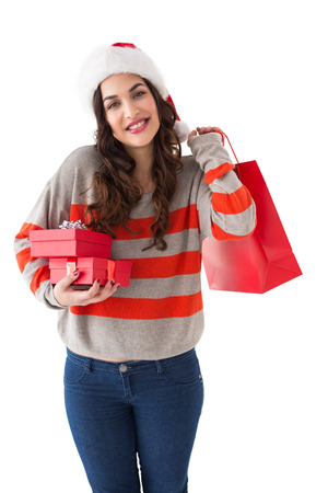 Smiling brunette holding gifts and showing shopping bag on white background photo