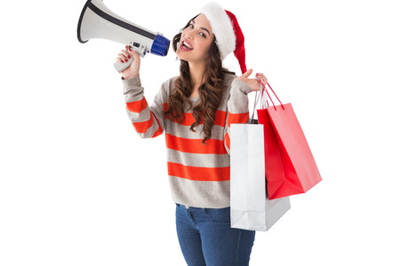 Festive brunette holding gift bags and megaphone on white background photo