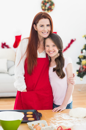 Festive mother and daughter baking together at home at christmas photo