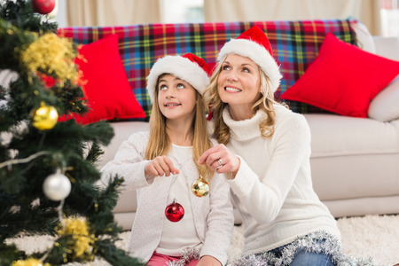 Festive mother and daughter decorating christmas tree at home in the living room photo