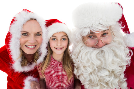 Santa and Mrs Claus smiling at camera with little girl on white background photo