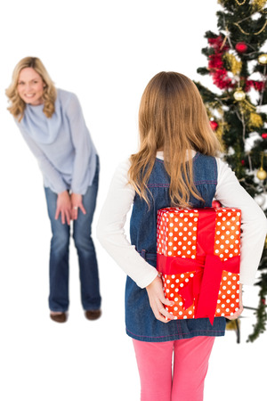 gift behind back: Little girl hiding christmas gift from mother on white background Stock Photo