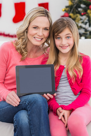 Festive mother and daughter showing tablet screen at home in the living room photo