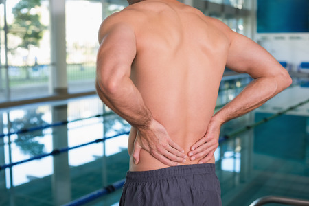 spinal conditions: Close up mid section of a shirtless fit swimmer with back ache by the pool Stock Photo