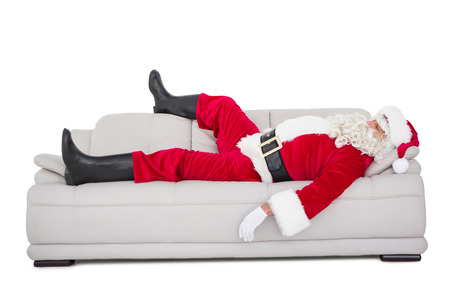 Santa claus sleeping on the couch on white background Stock Photo