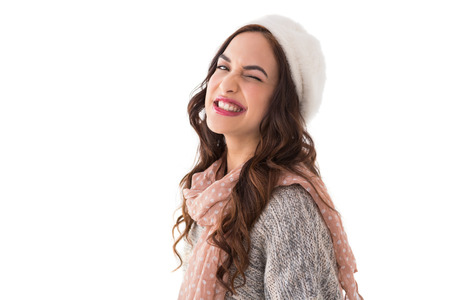 Brunette in winter clothes winking her eye on white background