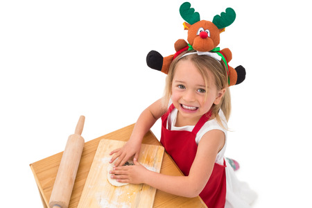 Festive little girl making cookies on white background photo