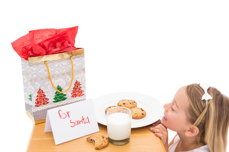 Milk and cookies left out for santa on white background photo