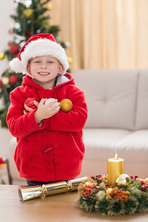 Festive little boy smiling at camera at home in the living room photo