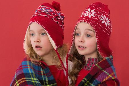 Festive little girls under a blanket on red background photo