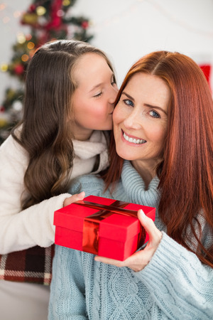 Daughter giving her mother a christmas present at home in the living room photo