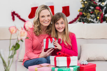 Festive mother and daughter with gift at home in the living room photo