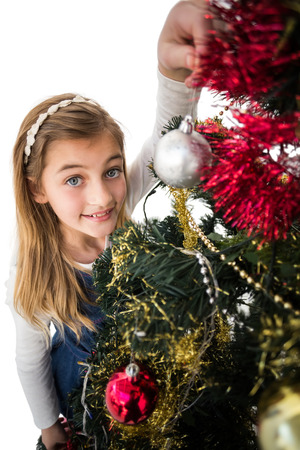 Festive little girl decorating christmas tree on white background photo