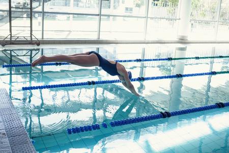 nataci�n: Vista lateral de un salto del nadador encajar en la piscina en el centro de ocio