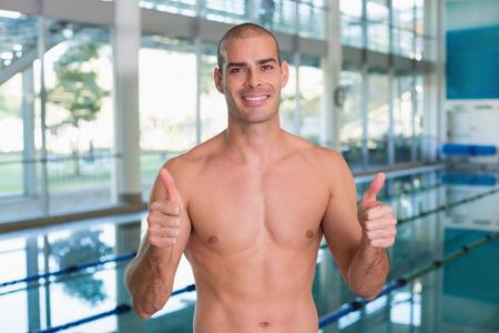 fitness hombres: Retrato de un nadador ajuste señalando los pulgares para arriba en la piscina en el centro de ocio