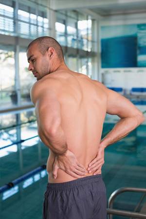 spinal conditions: Rear view of a shirtless fit swimmer with back ache by the pool