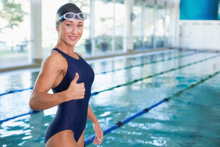 Portrait of a fit female swimmer gesturing thumbs up by the pool at leisure center