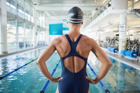 レジャー センターでプールでフィットの女子水泳選手の立っている後姿