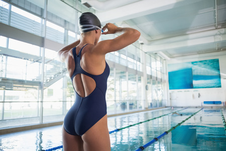 Rear view of a fit female swimmer standing by the pool at leisure center Stock Photo
