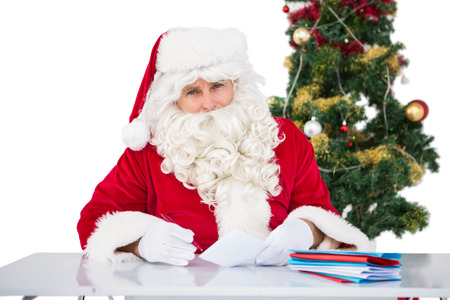 Portrait of father christmas writing list on white background photo