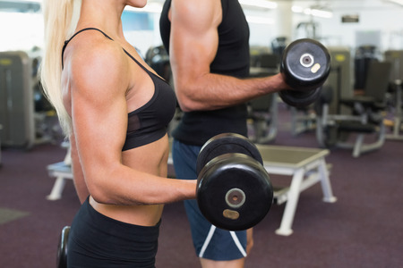 Side view mid section of a couple exercising with dumbbells in the gym photo
