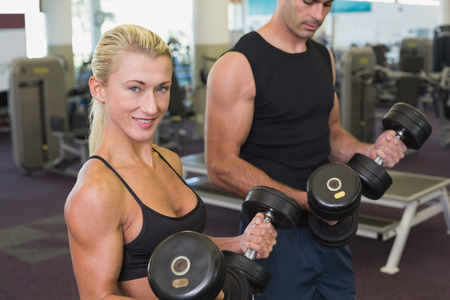 Side view of a couple exercising with dumbbells in the gym photo
