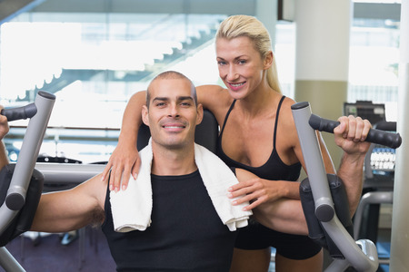 Smiling female trainer assisting man on fitness machine at the gym photo
