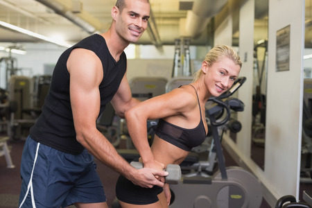Side view of a male trainer assisting woman with dumbbell in the gym photo