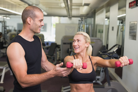 Smiling male trainer assisting woman with dumbbell in the gym photo