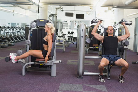 machines: Side view of fit young couple using fitness machines at the gym Stock Photo