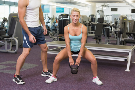 Male trainer assisting woman with kettle bell in the gym photo