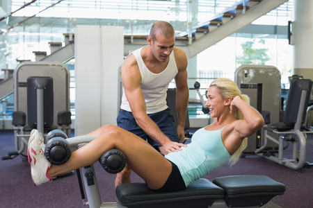 Side view of a male trainer assisting woman with abdominal crunches at the gym