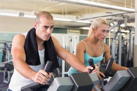 Determined fit young couple working on exercise bikes at the gym Stock Photo
