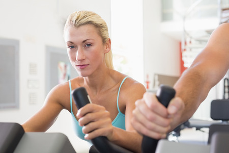 Close up of a fit young couple working on exercise bikes at the gym photo