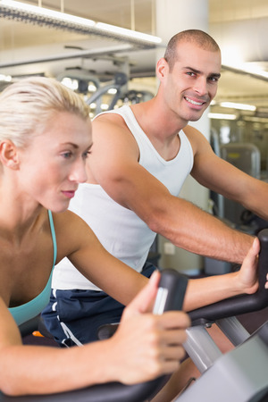 Side view of a fit young couple working on exercise bikes at the gym