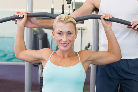 griping: Portrait of a beautiful young woman exercising on a lat machine in gym