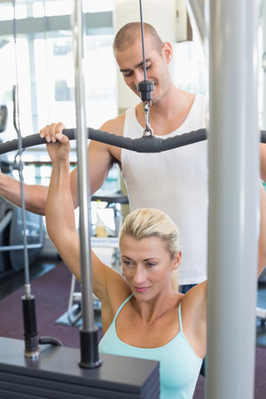 lat: Male trainer assisting beautiful young woman on a lat machine in gym