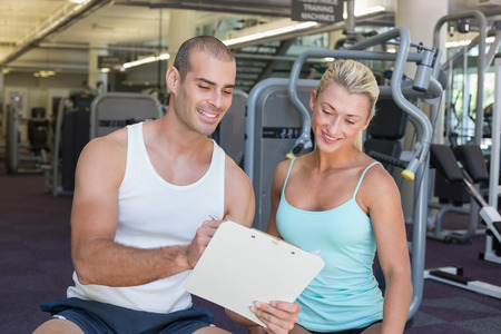 Beautiful young woman discussing her performance on clipboard with a trainer at the gym