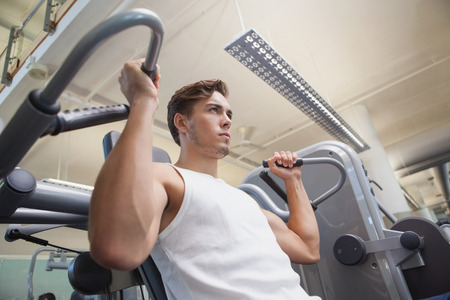 Fit man using weights machine for arms at the gym