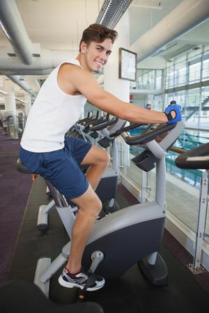man working out: Hombre apto que se resuelve en la bicicleta de ejercicio en el gimnasio