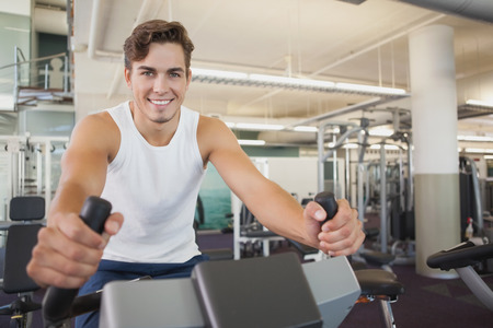 man working out: Fit man working out on the exercise bike at the gym