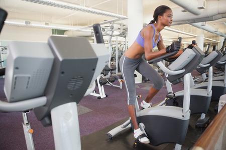 andando en bicicleta: Mujer apta que se resuelve en la bicicleta est�tica en el gimnasio
