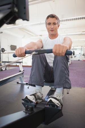 man working out: Hombre apto que se resuelve en la m�quina de remo en el gimnasio