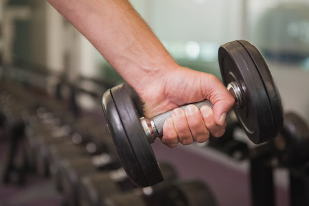part body: Fit man lifting heavy black dumbbell at the gym