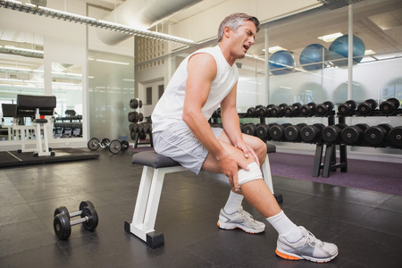 pain: Injured man gripping his knee in the weights room at the gym Stock Photo